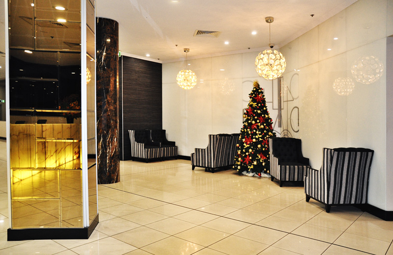 Meriton Suites Bondi Junction lobby with Christmas tree decorations.