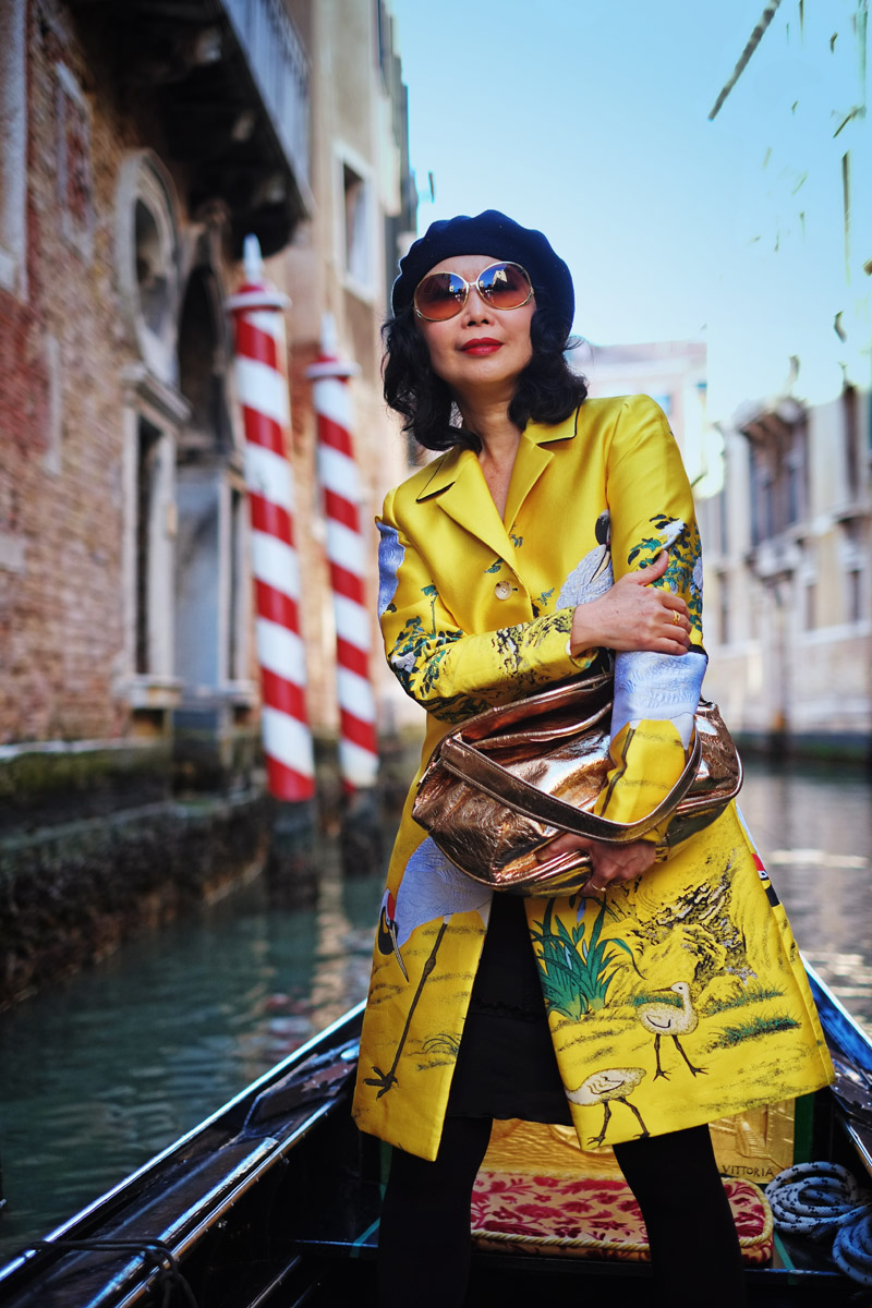 Chinese Empress style golden yellow jacket worn and styled by Vivienne She for White Caviar Life. Fashion shoot on a Venetian gondola in Venice by fashion photographer Kent Johnson.